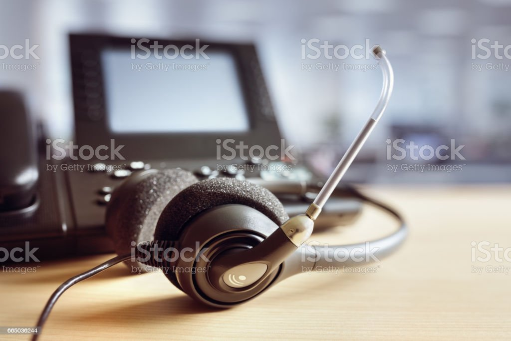 Headset headphones and telephone in call center stock photo