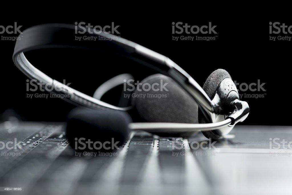 Headset lying on laptop computer keyboard stock photo