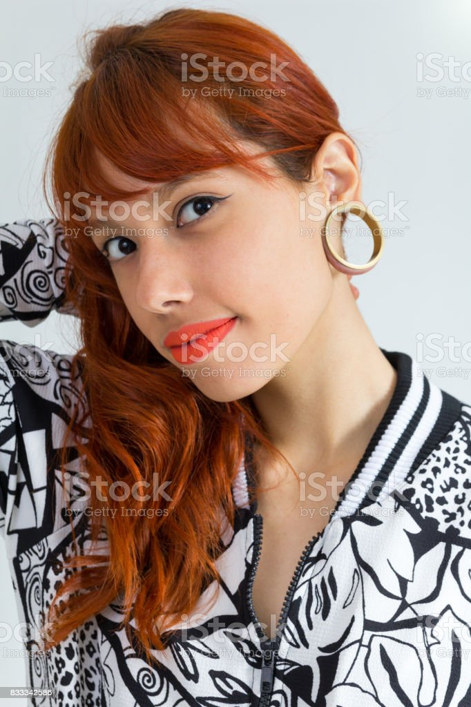 Headshot. Ear reamer. Redhead woman smiles and shows off her reamer earring. She wears black and white, neutral clothing. She is beautiful and charming. stock photo
