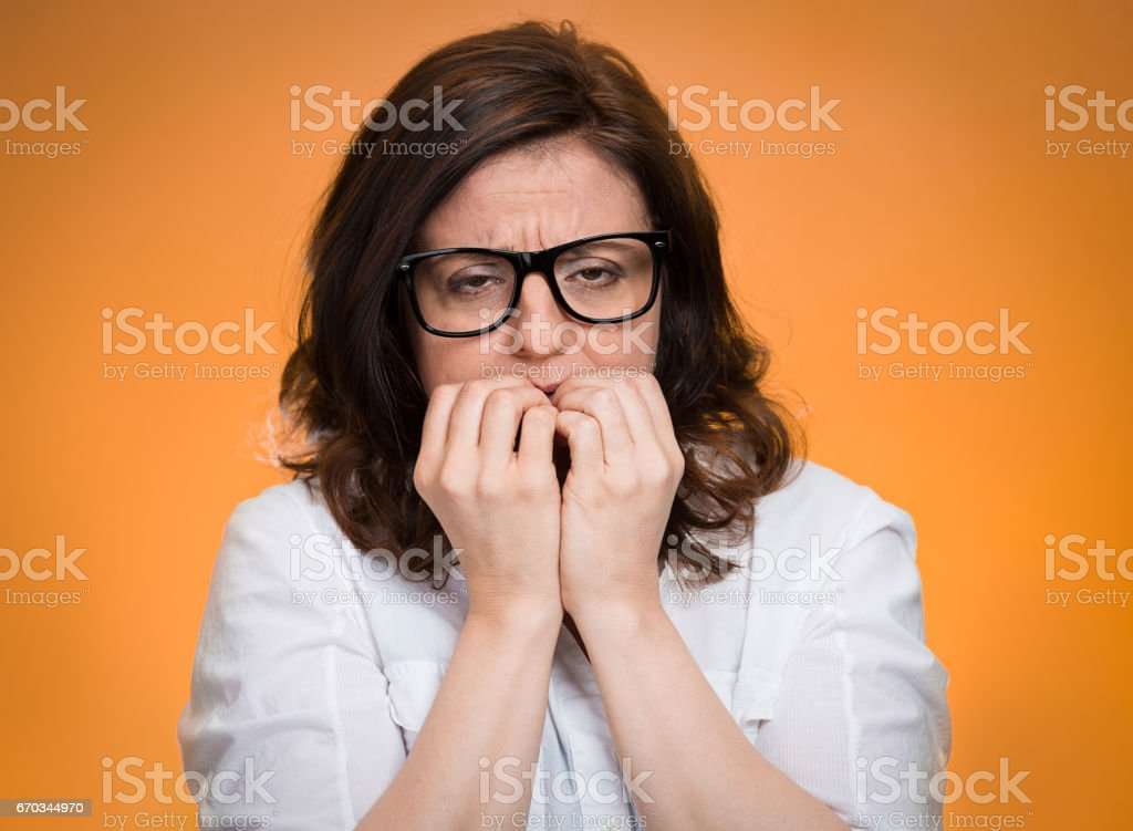 headshot nervous, stressed middle aged woman with glasses biting fingernails looking anxiously, stock photo