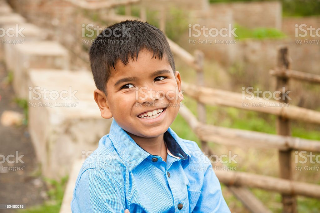 Headshot of cute Latin or Asian boy at park, street. stock photo