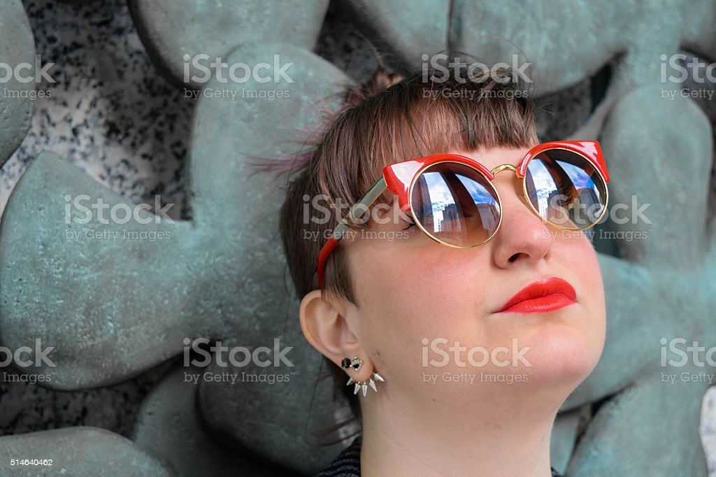 Head-shot of Successful Young White Female Wearing Sunglasses, Monochrome Background stock photo