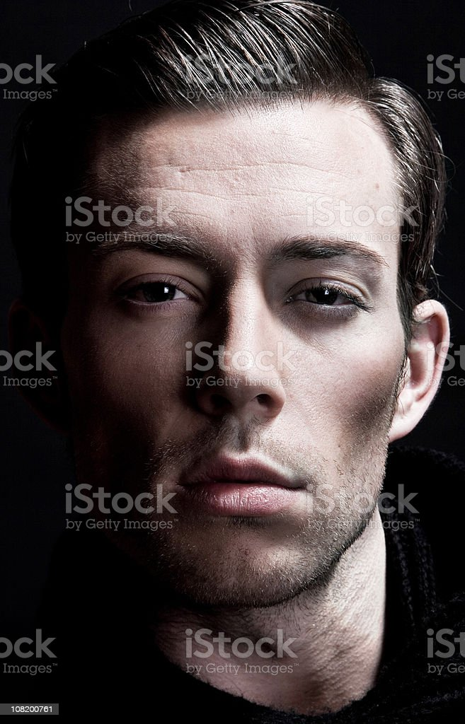 Headshot of Young Man with Strong Bone Structure, Low Key stock photo