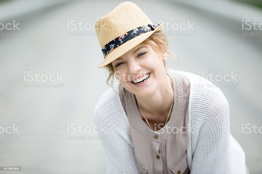 Headshot portrait of young happy woman laughing outdoors stock photo
