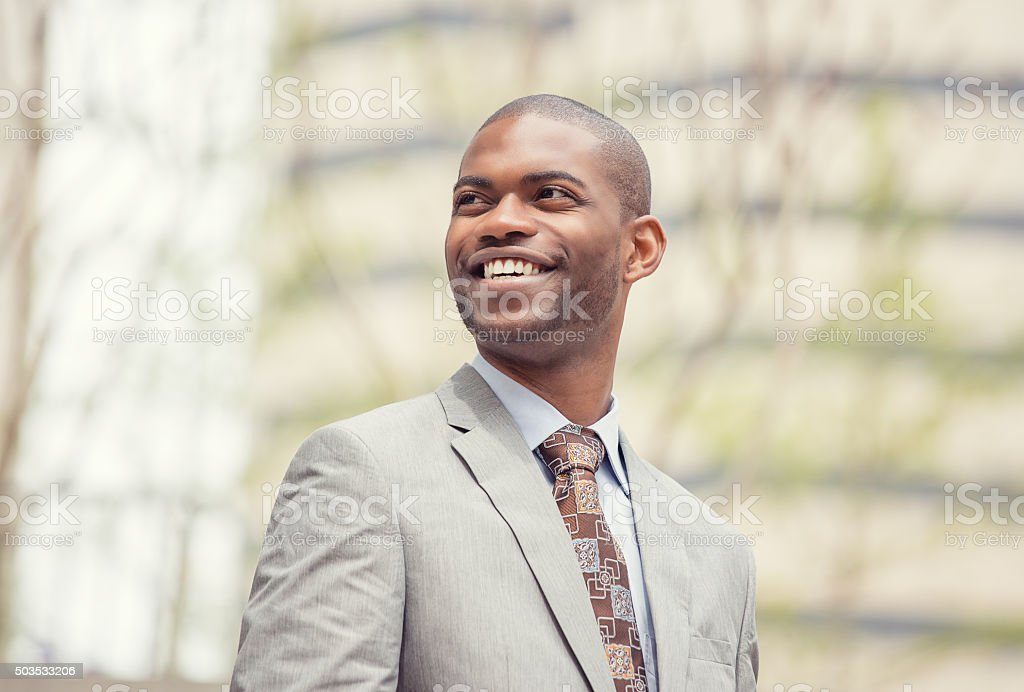 Headshot young professional man smiling laughing outdoors stock photo