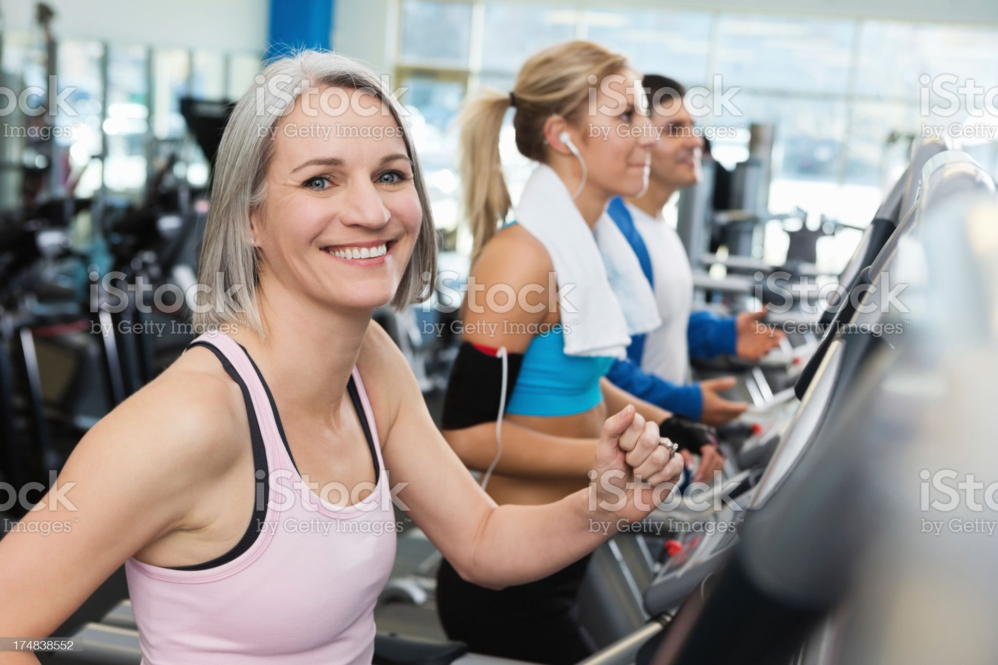Healhty mature woman walking on treadmill in gym royalty-free stock photo