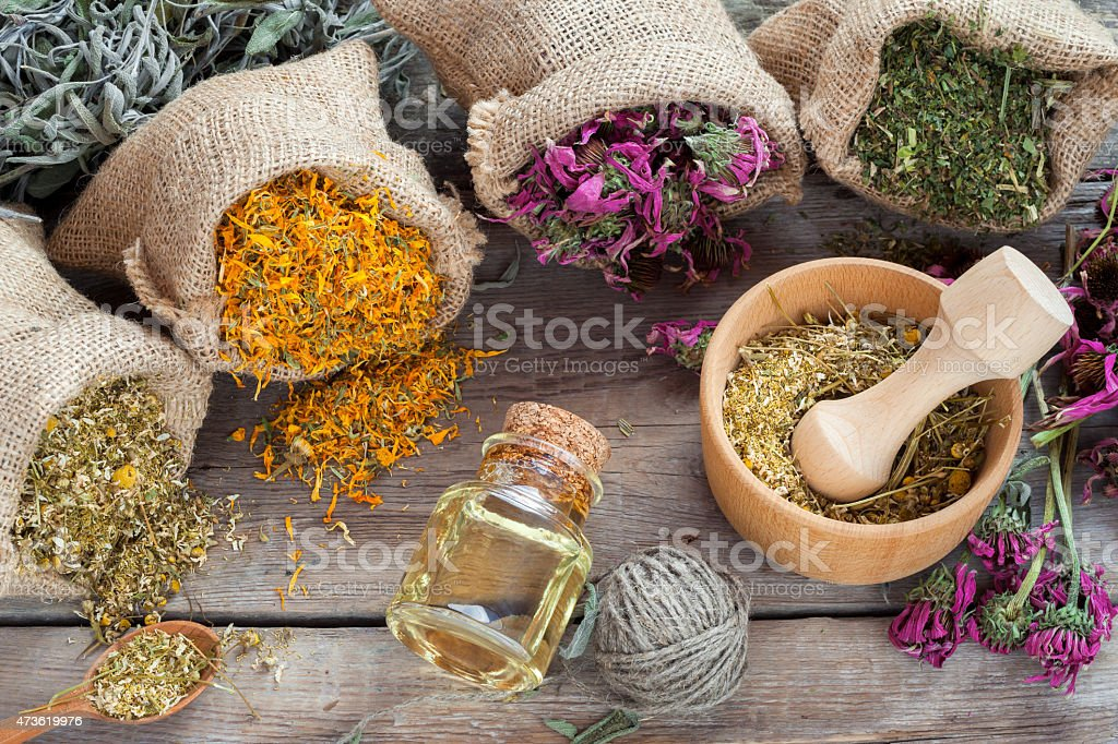 Healing herbs in hessian bags and mortar with chamomile stock photo