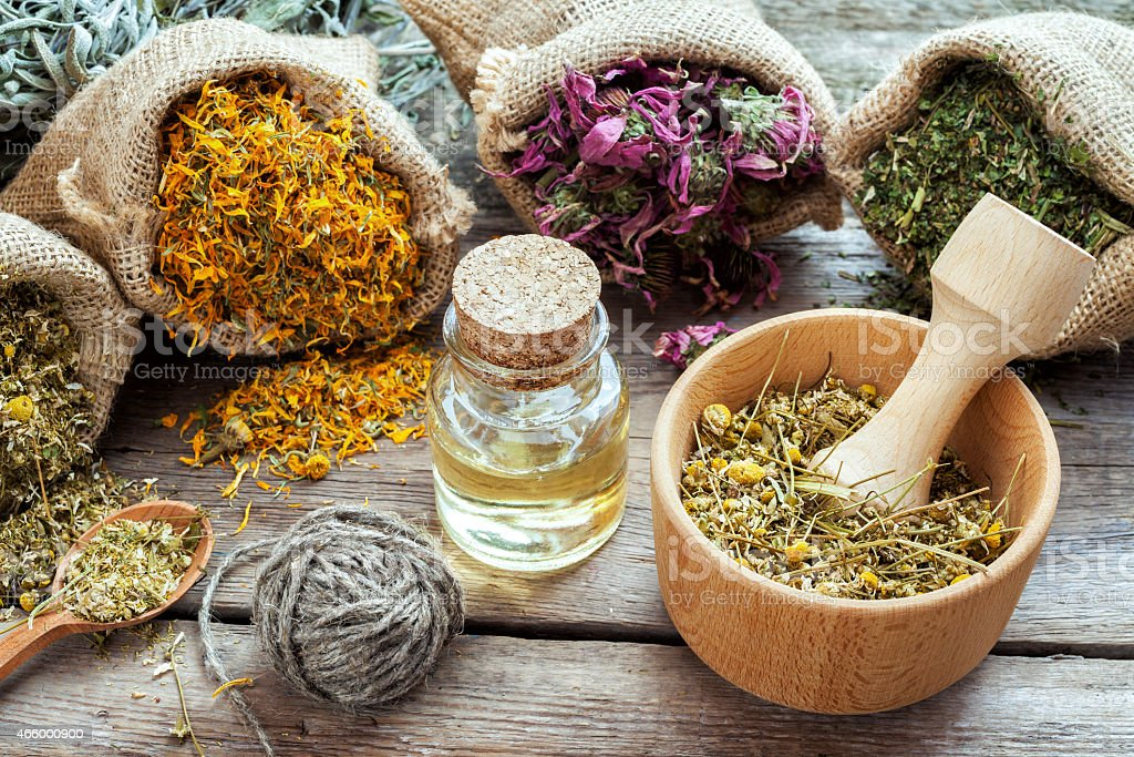 Healing herbs in hessian bags, mortar with chamomile and oil stock photo