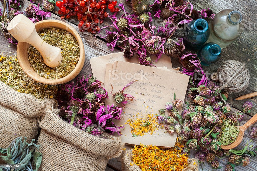 Healing herbs in hessian bags, wooden mortar and bottles stock photo