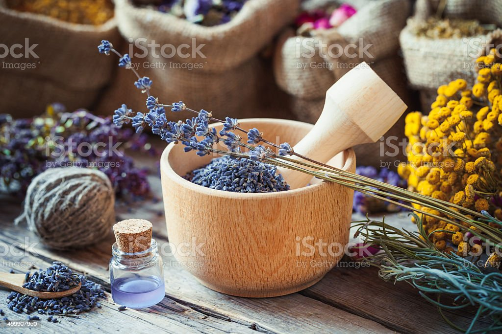 Healing herbs in hessian bags, wooden mortar with lavender stock photo