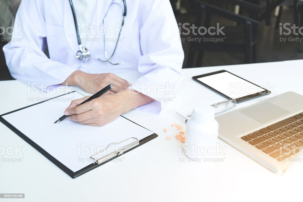 Health care and Medical concept, Female doctor hand hold pen filling patient history list at clipboard pad to recommend treat of patient stock photo