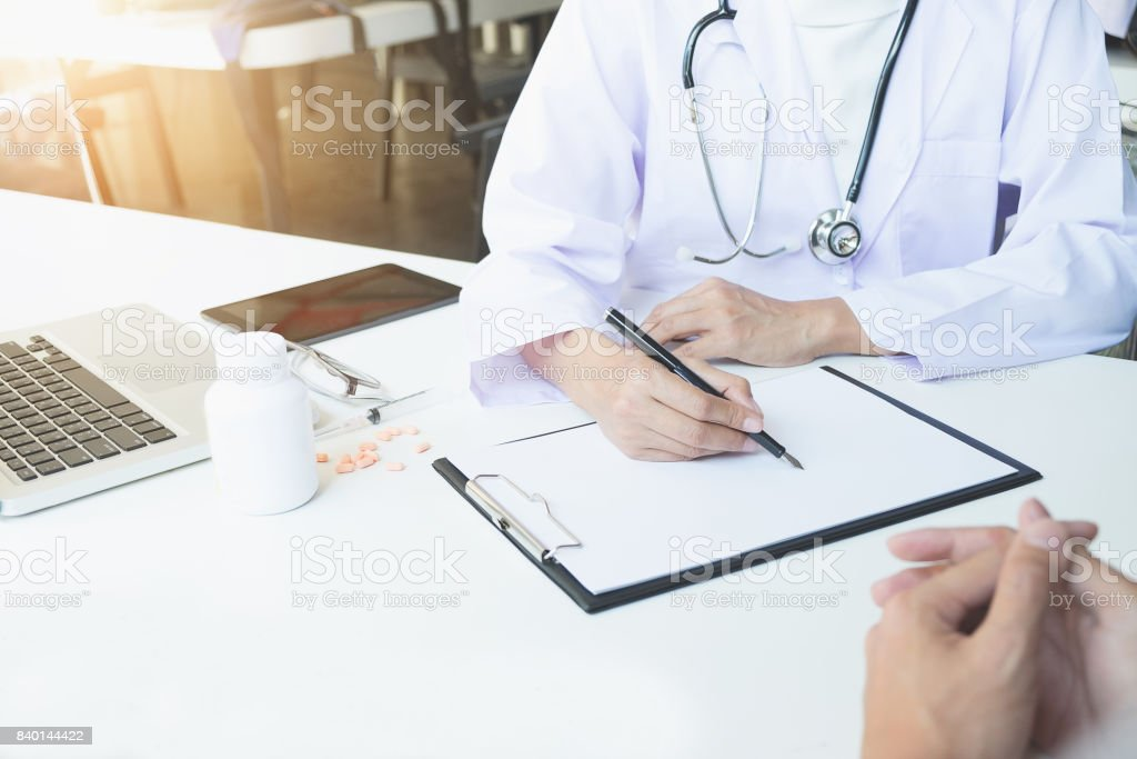 Health care and Medical concept, patient listening intently to a female doctor explaining patient symptoms or asking a question as they discuss paperwork together in a consultation stock photo