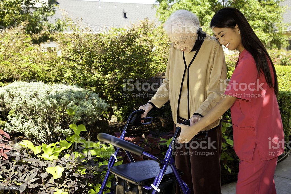 Health Care Nurse Helping Senior Adult Lady With Her Walker royalty-free stock photo