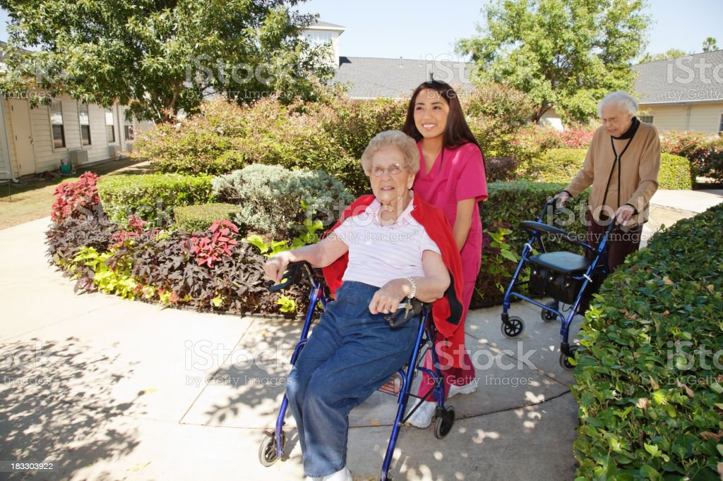 Health Care Nurse Helping Senior Adults Outside royalty-free stock photo