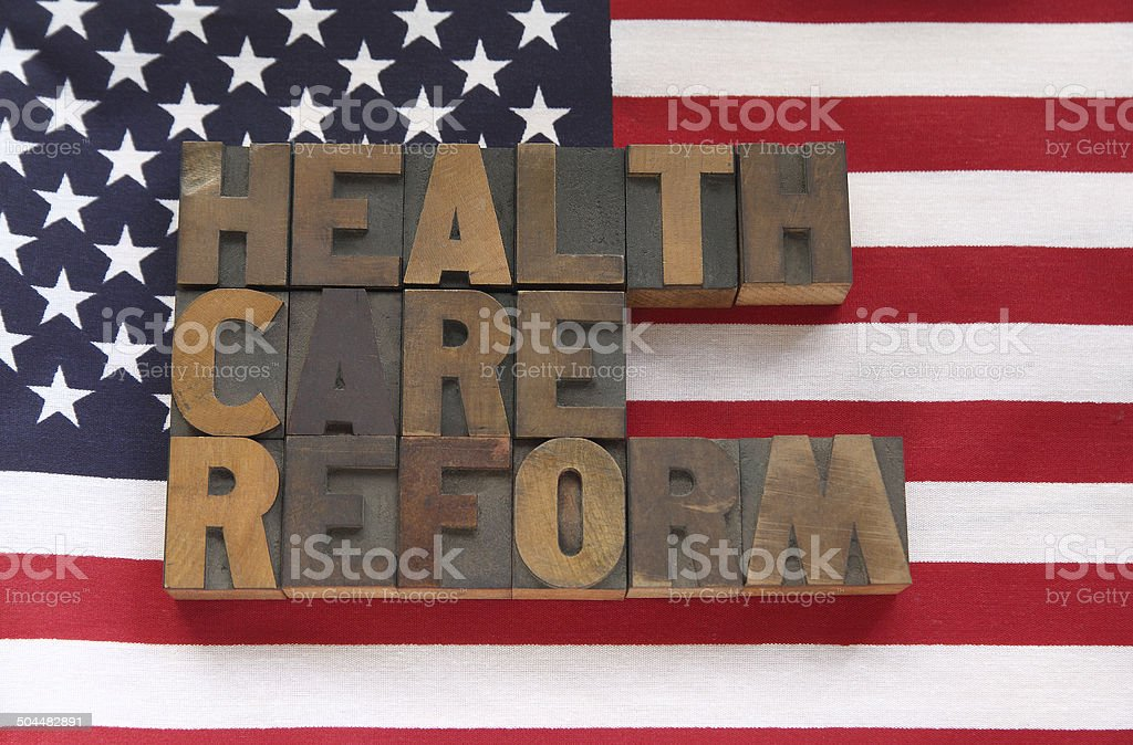 health care reform in wood type on flag stock photo