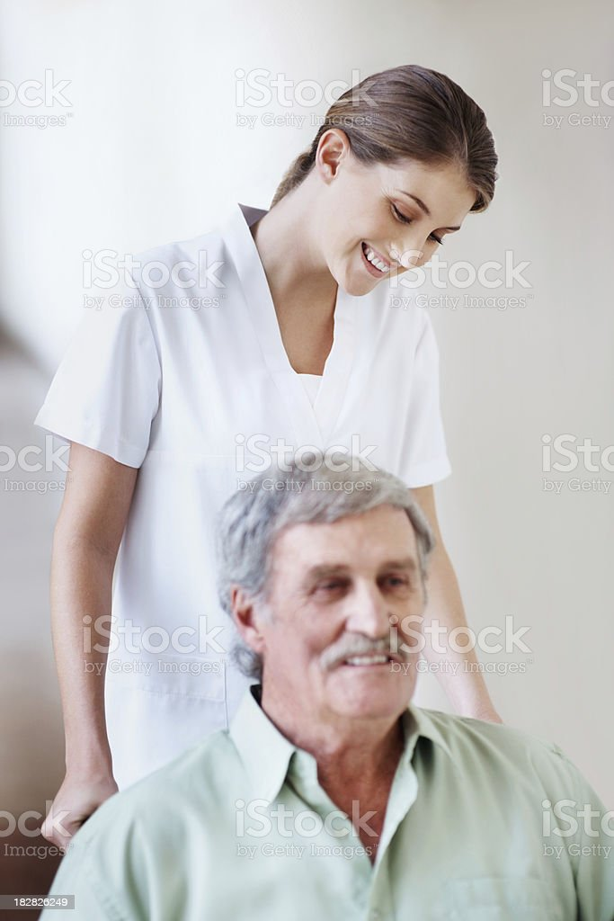 Health care worker pushing an elderly man on a wheelchair royalty-free stock photo