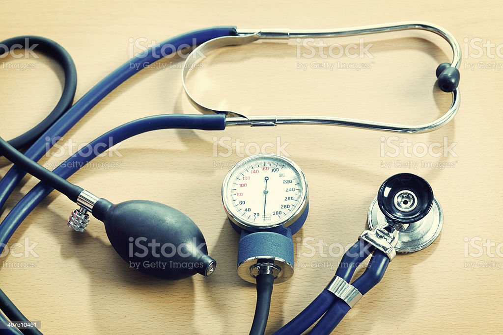 Health check-up equipment: stethoscope and blood pressure gauge stock photo