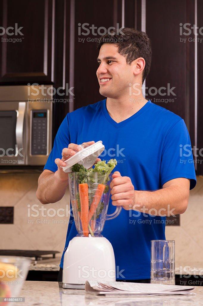 Health conscious man prepares veggie smoothie. stock photo