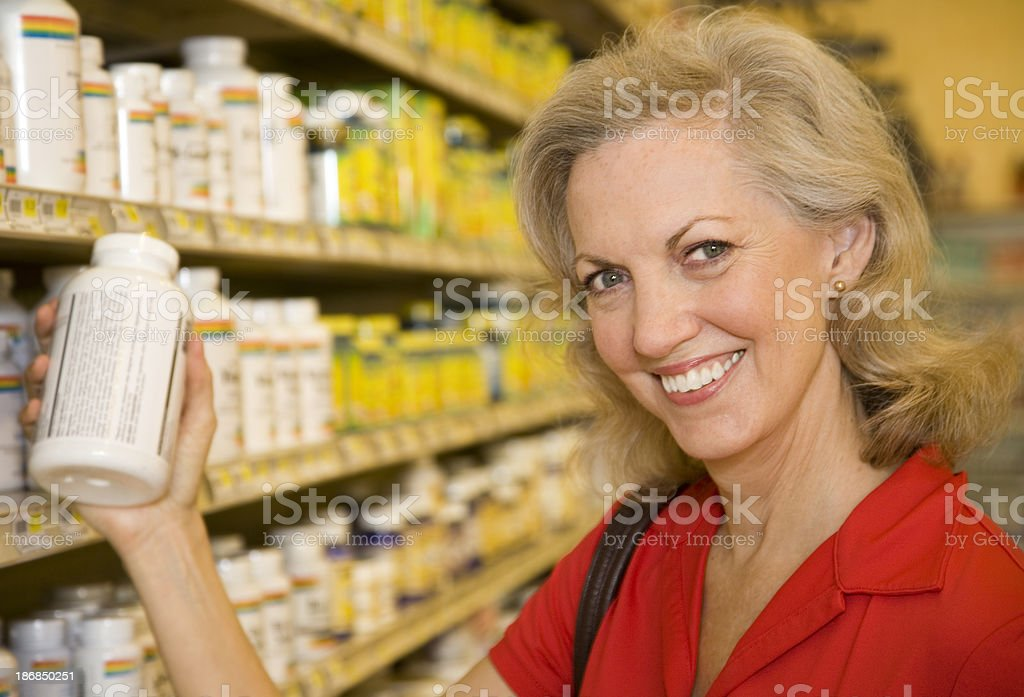 Health Conscious Shopper Checking Vitamin Bottle at the Store royalty-free stock photo