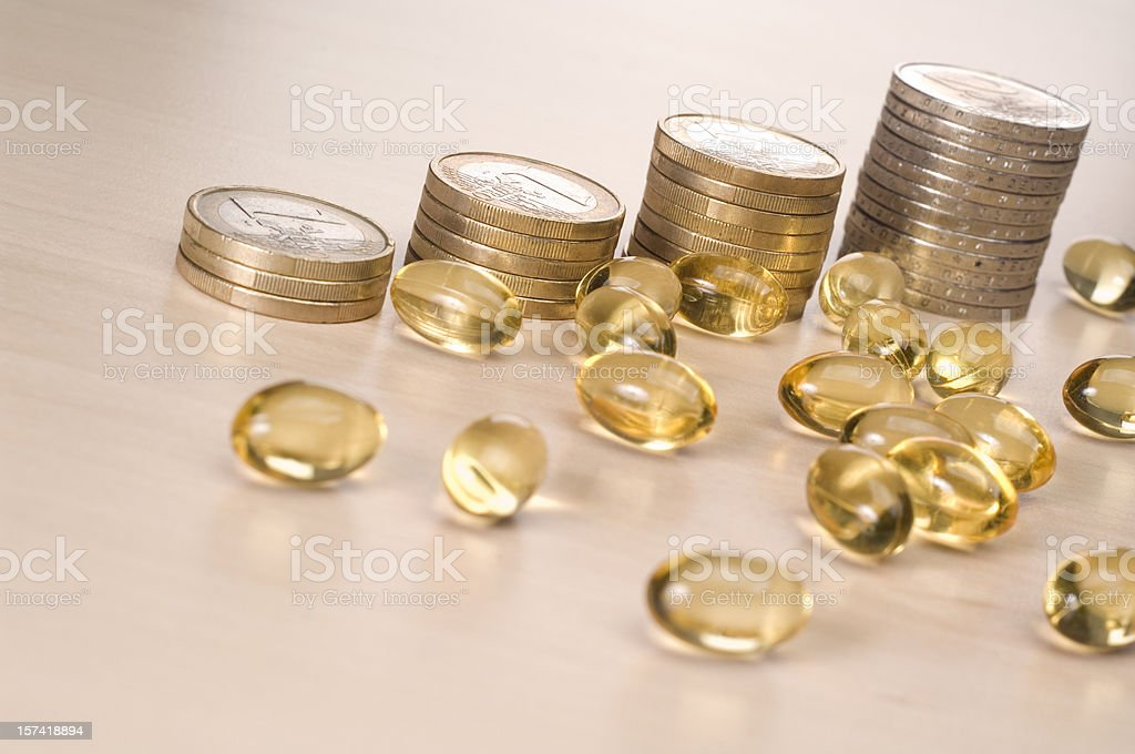 Health Cost, Pound coins and medical pills royalty-free stock photo