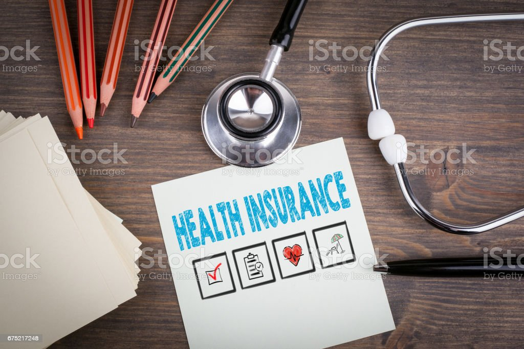 Health Insurance. Workplace of a doctor. Stethoscope on wooden desk. stock photo