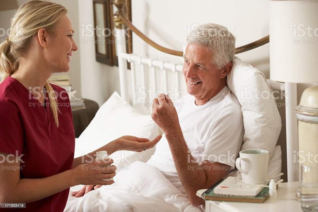Health Visitor Giving Senior Male Medication In Bed stock photo