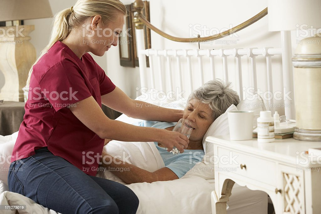 Health Visitor Giving Senior Woman Glass Of Water In Bed stock photo