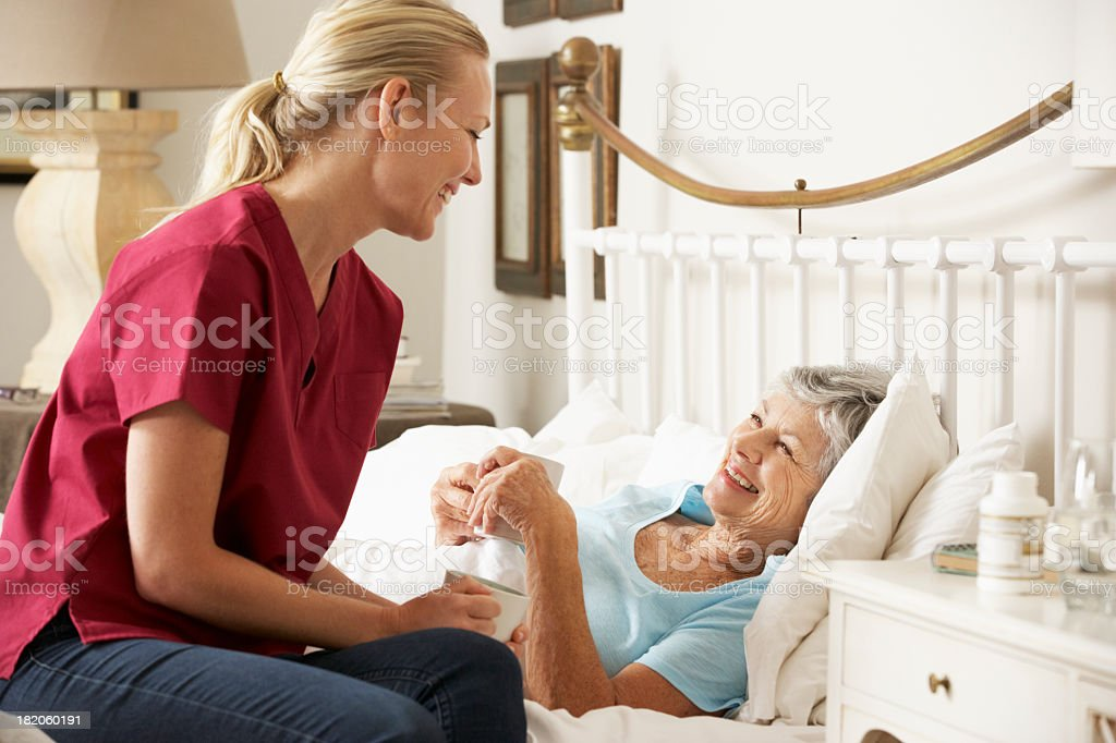 Health Visitor Talking To Senior Woman Patient In Bed stock photo