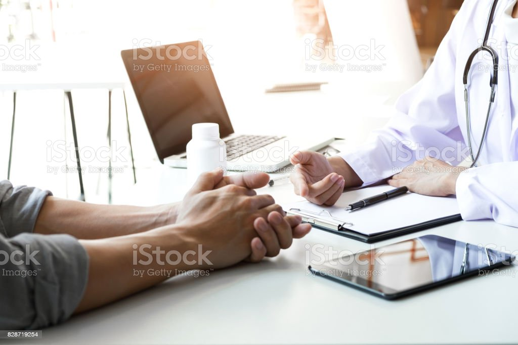 Healthcare and Medical concept, patient listening intently to a female doctor explaining patient symptoms or asking a question as they discuss paperwork together in a consultation stock photo