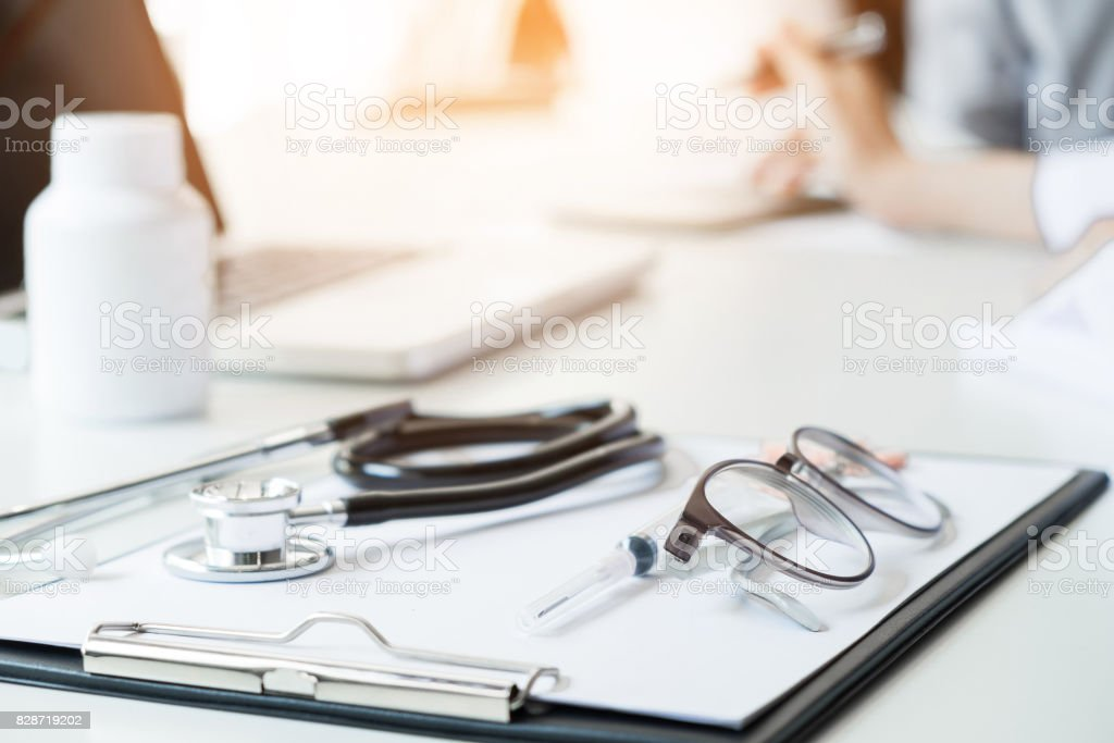 Healthcare and Medical concept, View of stethoscope and equipment on foreground table with patient listening intently to a female doctor as they discuss paperwork together in a consultation. stock photo