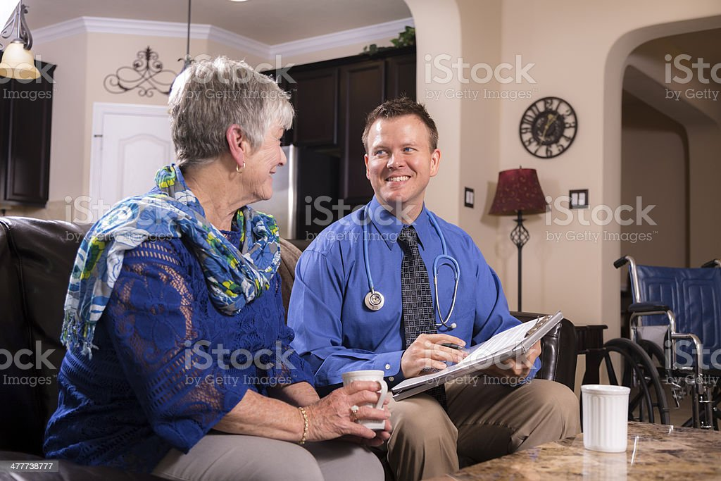 Healthcare: Concierge doctor visits senior woman at home. royalty-free stock photo