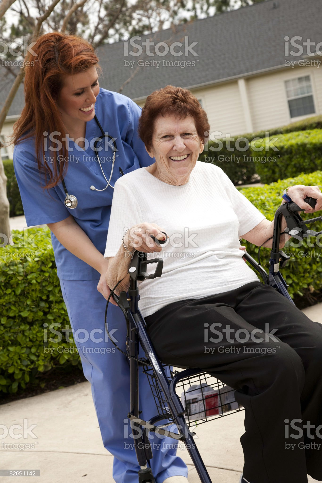 Healthcare Helper Assisting Elderly Lady on Her Walker/Rider royalty-free stock photo