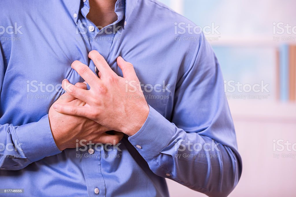 Healthcare: Man clutching his chest in pain, possible heart attack. stock photo