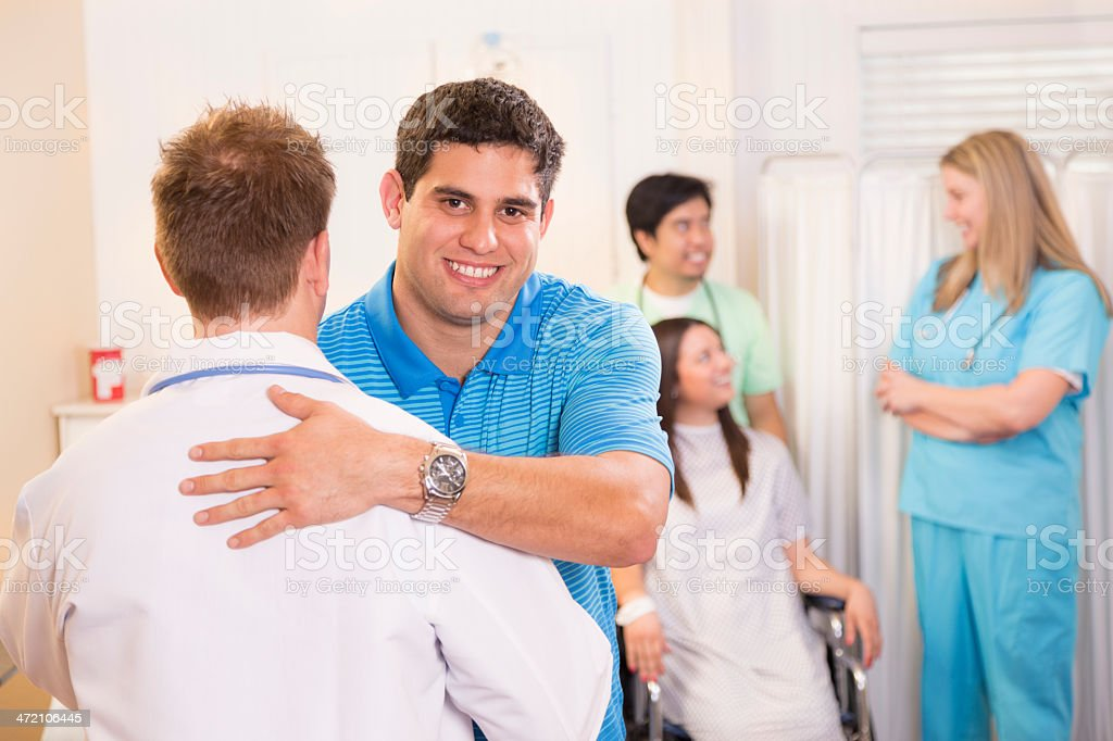 Healthcare: Man hugs doctor for taking care of patient. stock photo