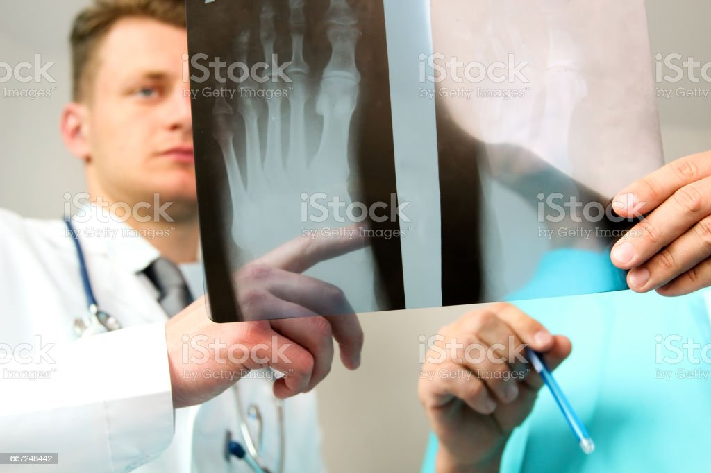 healthcare, medical and radiology concept -  Male doctors looking at x-ray of foot stock photo