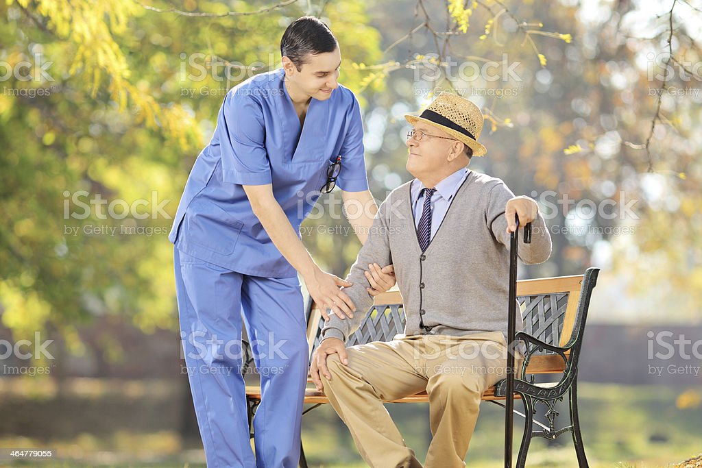 Healthcare professional talking with senior man outside stock photo