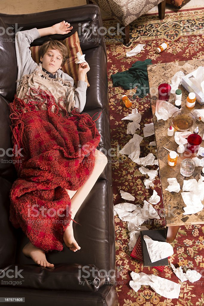 Healthcare: Sick boy lies on couch with the flu.  Medications. royalty-free stock photo