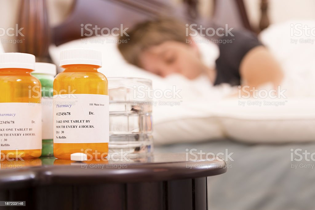 Healthcare:  Sick man in bed with the flu.  Medications. stock photo