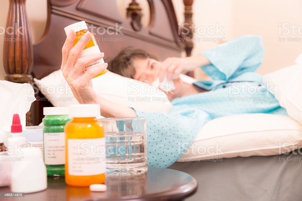 Healthcare:  Sick woman in bed with the flu.  Medications. royalty-free stock photo