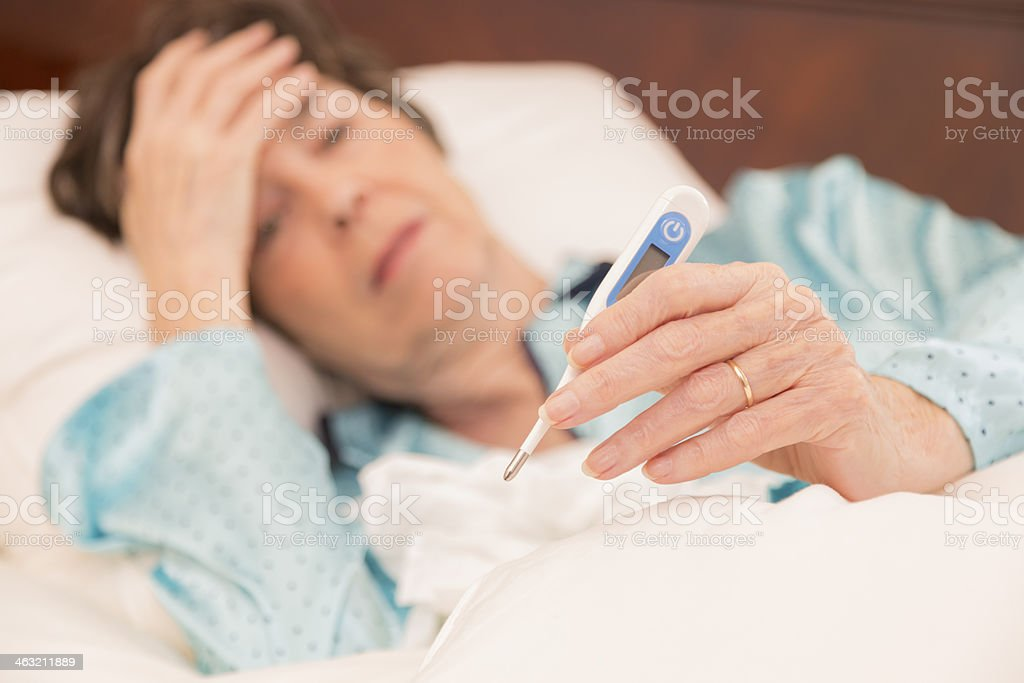 Healthcare:  Sick woman in bed with the flu. Thermometer. stock photo