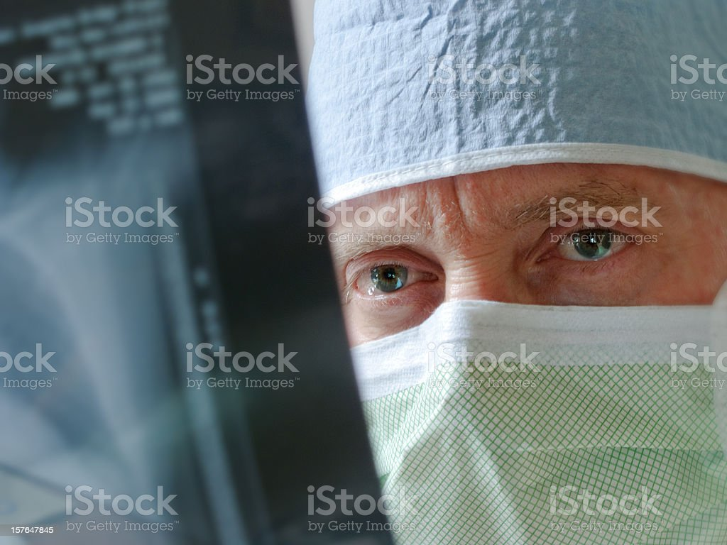 Healthcare Specialist Physician Surgeon Intensely Studies Xray Results before Surgery stock photo