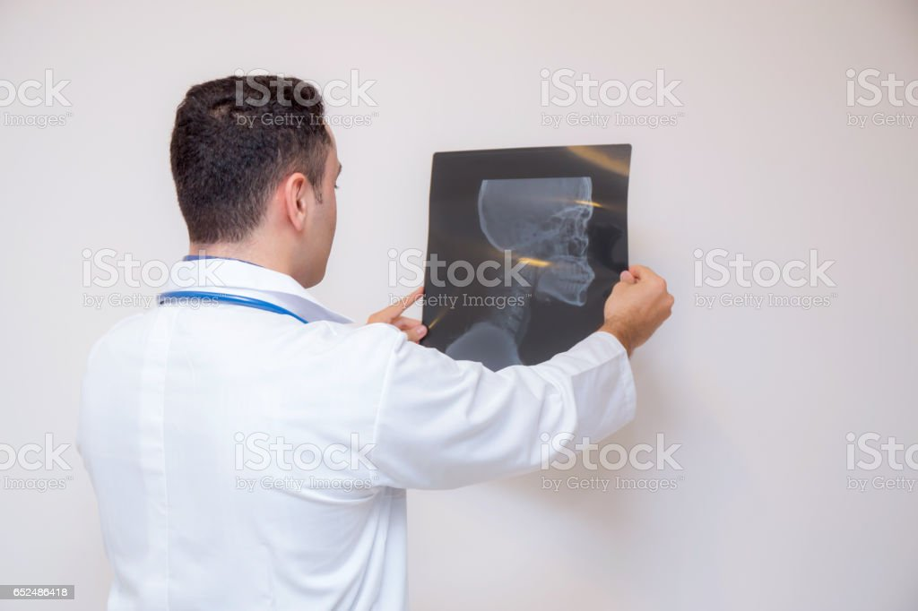 healthcare with roentgen - people and medicine concept - male doctor in white coat looking at x-ray isolated on white background stock photo