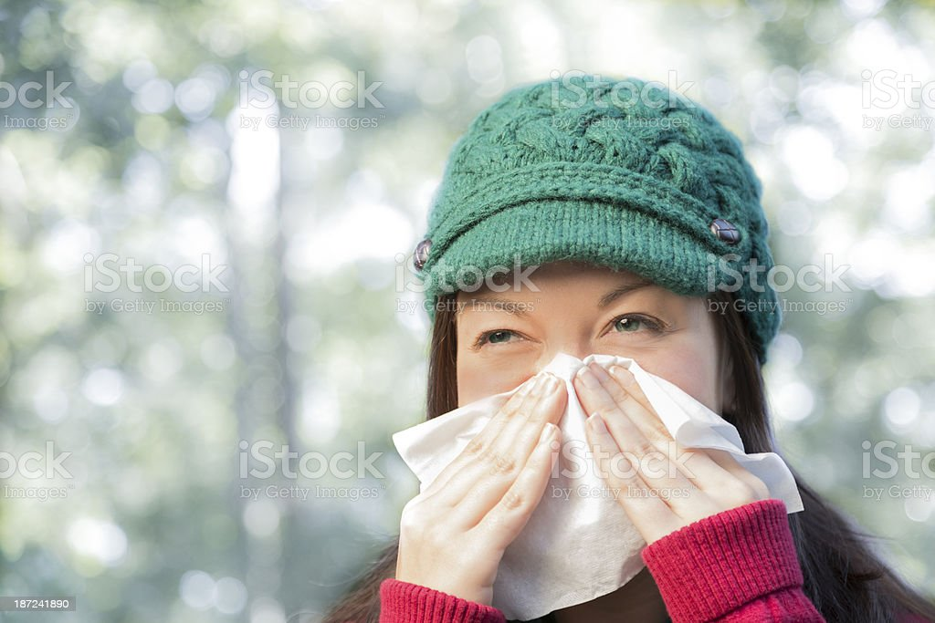 A sick young woman sneezes into a tissue while outside. She has the...