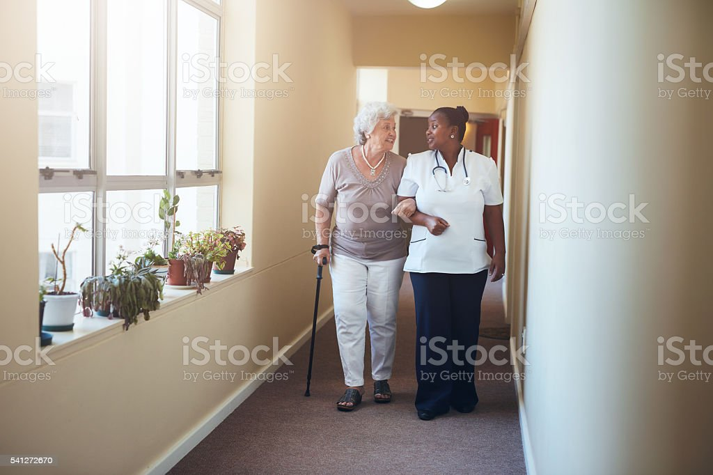 Healthcare work helping female patient. stock photo