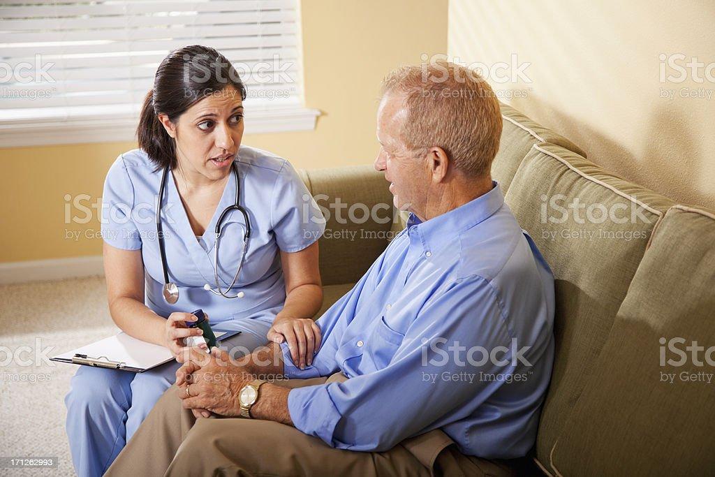 Healthcare worker advising patient on prescription medicine stock photo