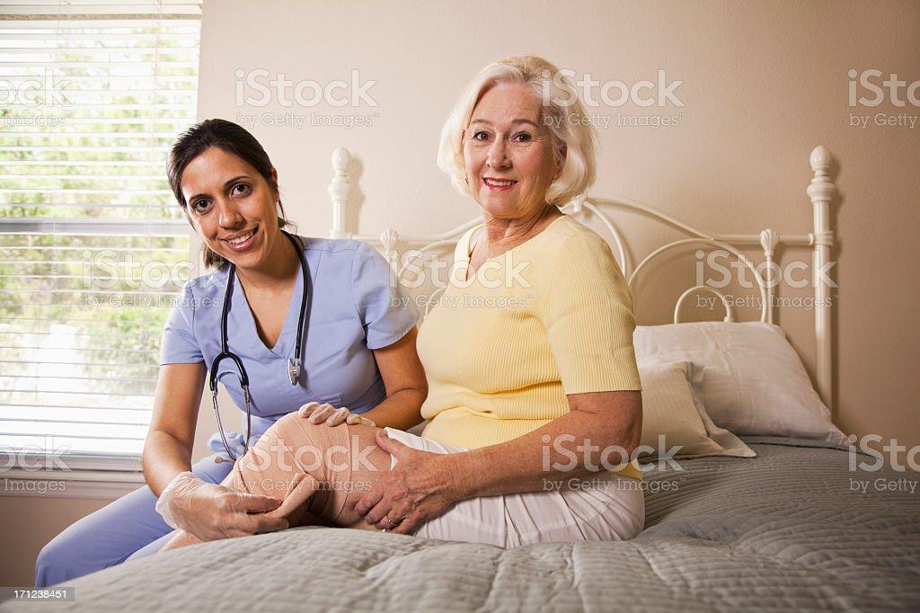 Healthcare worker bandaging patient's knee stock photo