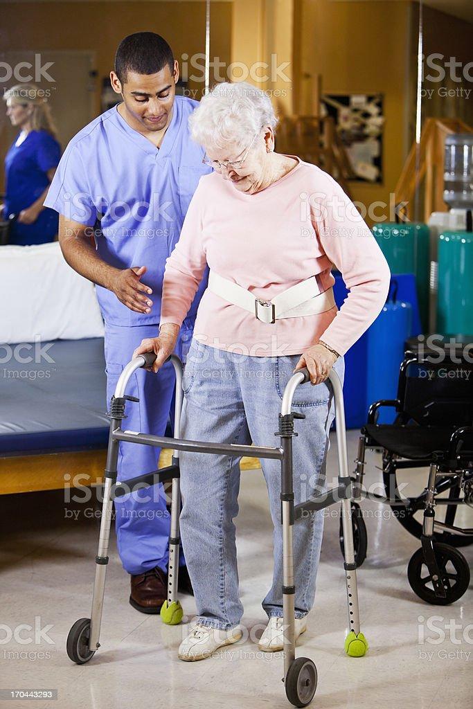 Healthcare worker helping senior woman use walker stock photo