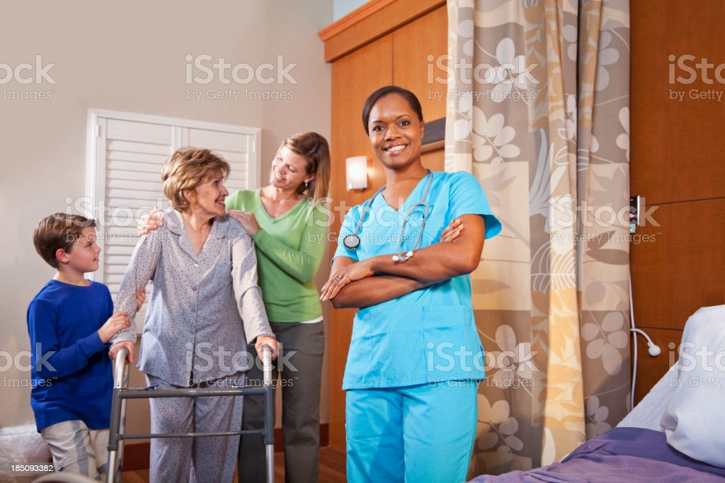 Healthcare worker in hospital room with senior patient and famil stock photo