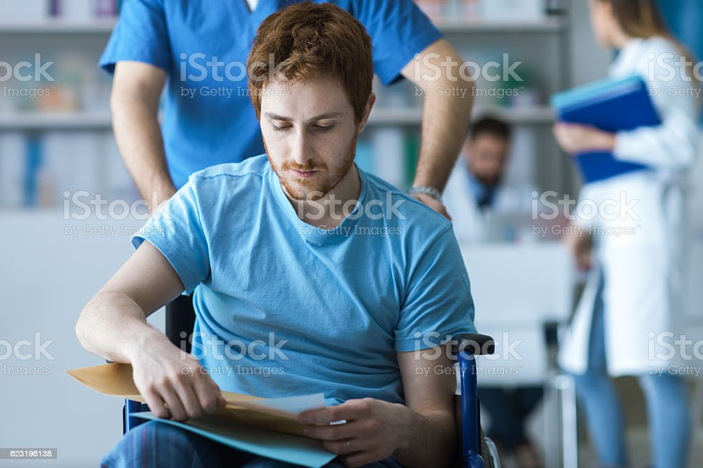 Healthcare worker pushing a man in wheelchair stock photo