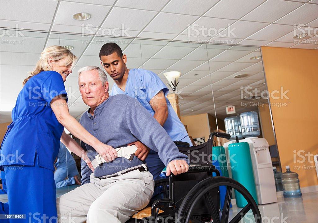 Healthcare workers helping patient into wheelchair royalty-free stock photo